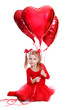 Ballerina like dressed girl sitting with red heart shaped balloo