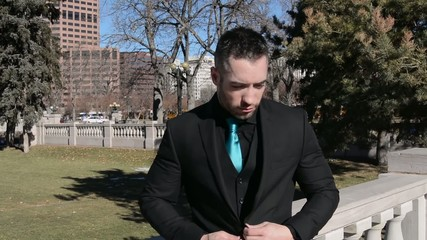 Young man buttoning his suit jacket outdoors