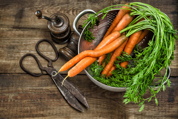 Fresh carrots with vintage kitchen utensils. Country style food