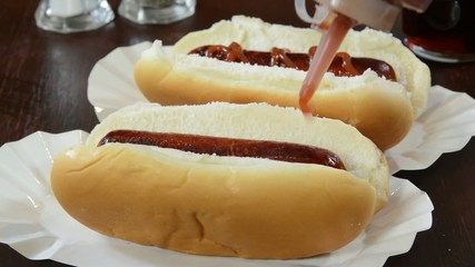 pouring catsup onto hot dogs