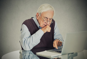Elderly old man using laptop computer sitting at table