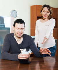 Man counting money, wife watching him