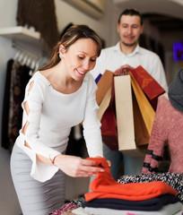 Ordinary couple choosing clothes at market