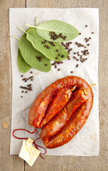 italian SPICY sausage, sage leaves and peppercorn on wooden tabl