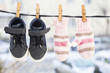 Pink gloves and shoes of a child hanging on the clothespin