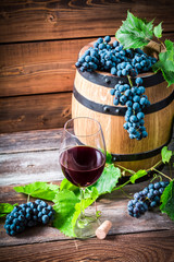 Glass of red wine and grapes in a wooden cellar