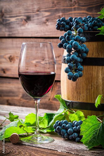 Red grapes and a glass of red wine - 78348163