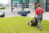 City landscaper cutting grass with gasoline lawn mower