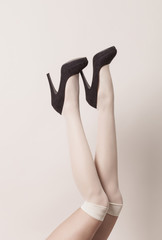 Female legs wearing white parisian stockings and black heels