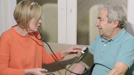 Nurse Checks Senior Blood Pressure, Close up