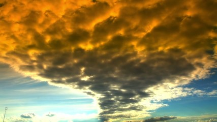timelapse of orange clouds in summer in blue sky with sun