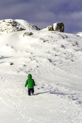 A brave little boy trying to climb a rock,on snow, in winter