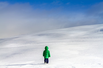 An adventurous little boy walking in the clouds in winter