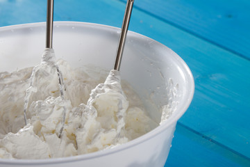 Whipped Cream and whisk in Plastic Bowl