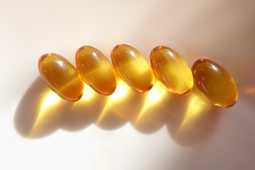 Gold vitamin gel capsules on white plate