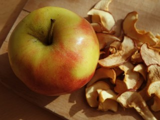 Whole apple and dried apple slices on chopping board top view