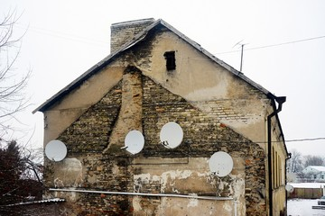 Satellite dish on the wall of a old house