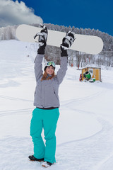 Junge Frau in Siegerhaltung , hebt Ihr Snowboard in die Luft.
