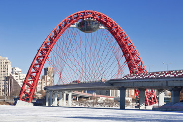 Red bridge over the frozen Moskva river, Moscow, Russia