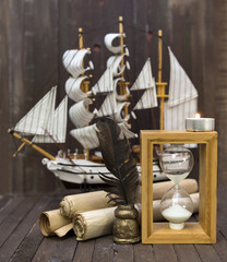 Sea still life with paper scrolls, ship and sand glass