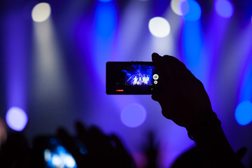 People at concert shooting video or photo.