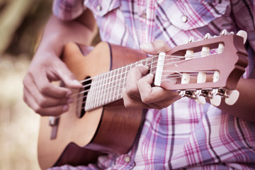 Male hand playing guitarlele on meadow background in retro style