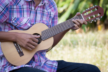 Male hand playing guitarlele on meadow background