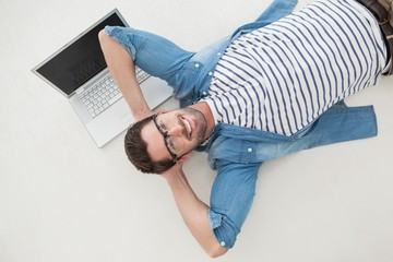 Relaxed casual businessman lying on his laptop