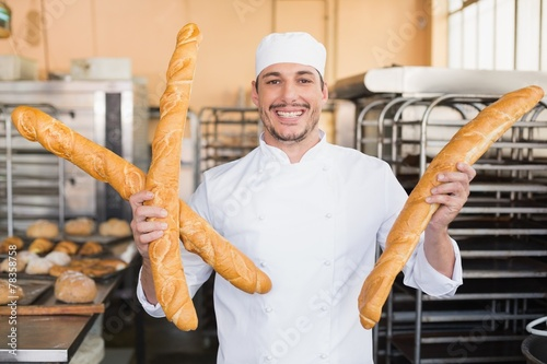 Papiers peints Table preparee Smiling baker holding three baguettes