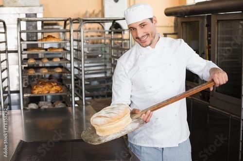 Leinwanddruck Bild Happy baker taking out fresh loaf