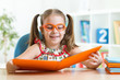 Happy funny child girl in glasses reading a book
