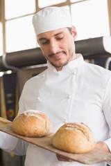 Baker showing tray of fresh bread