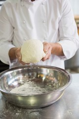 Baker forming dough in mixing bowl