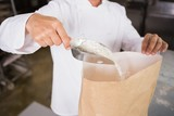 Close up of baker taking flour with a scoop