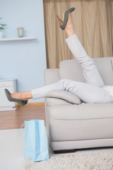 Legs of woman with heels lying on couch