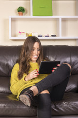 Pretty young woman using gadget while relaxing on sofa at home