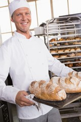 Baker holding tray of bread