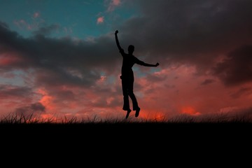 Composite image of silhouette of jumping woman