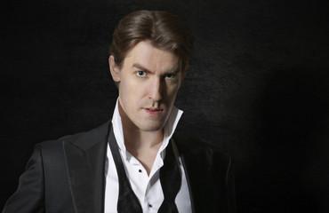 Elegant man in tuxedo with untied bow, dark background