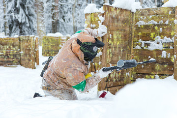 Man sitting on snow behind wooden fortification playing paintbal