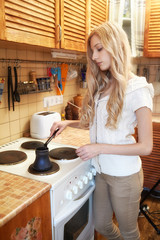Young blonde woman making coffee
