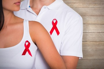 Composite image of couple supporting aids awareness together