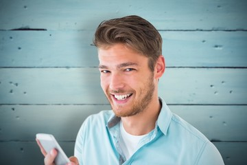 Composite image of handsome young man using his smartphone