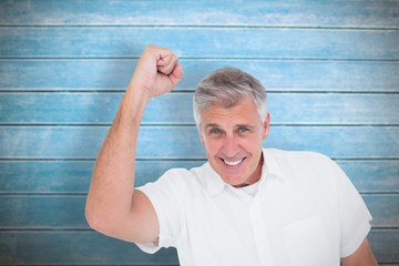 Composite image of casual man cheering at camera