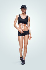 Fitness sporty woman on white background. Strong abs showing.