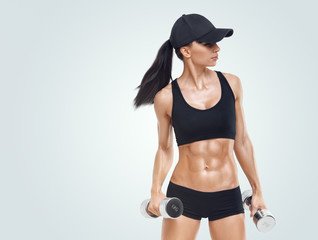 Fitness woman in training pumping up muscles with dumbbells