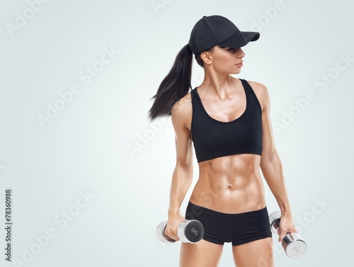 Fitness woman in training pumping up muscles with dumbbells - 78360988