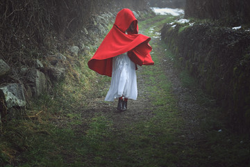 Red hooded woman on a dark country road