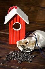 Red wooden bird house with seed