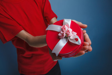 gift in a box in his hands on a gray background